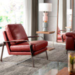 Armchair upholstered in leather with polished stainless steel legs