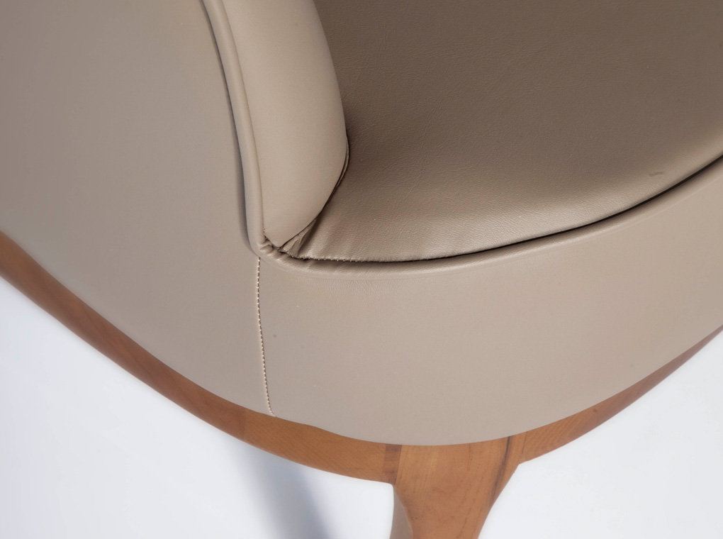 Upholstered armchair in  leatherette with walnut veneered wood legs